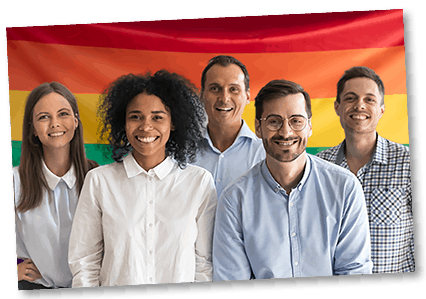 multi ethnic group of people standing in front of pride flag