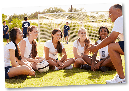 Group of female athletes with coach on soccer field